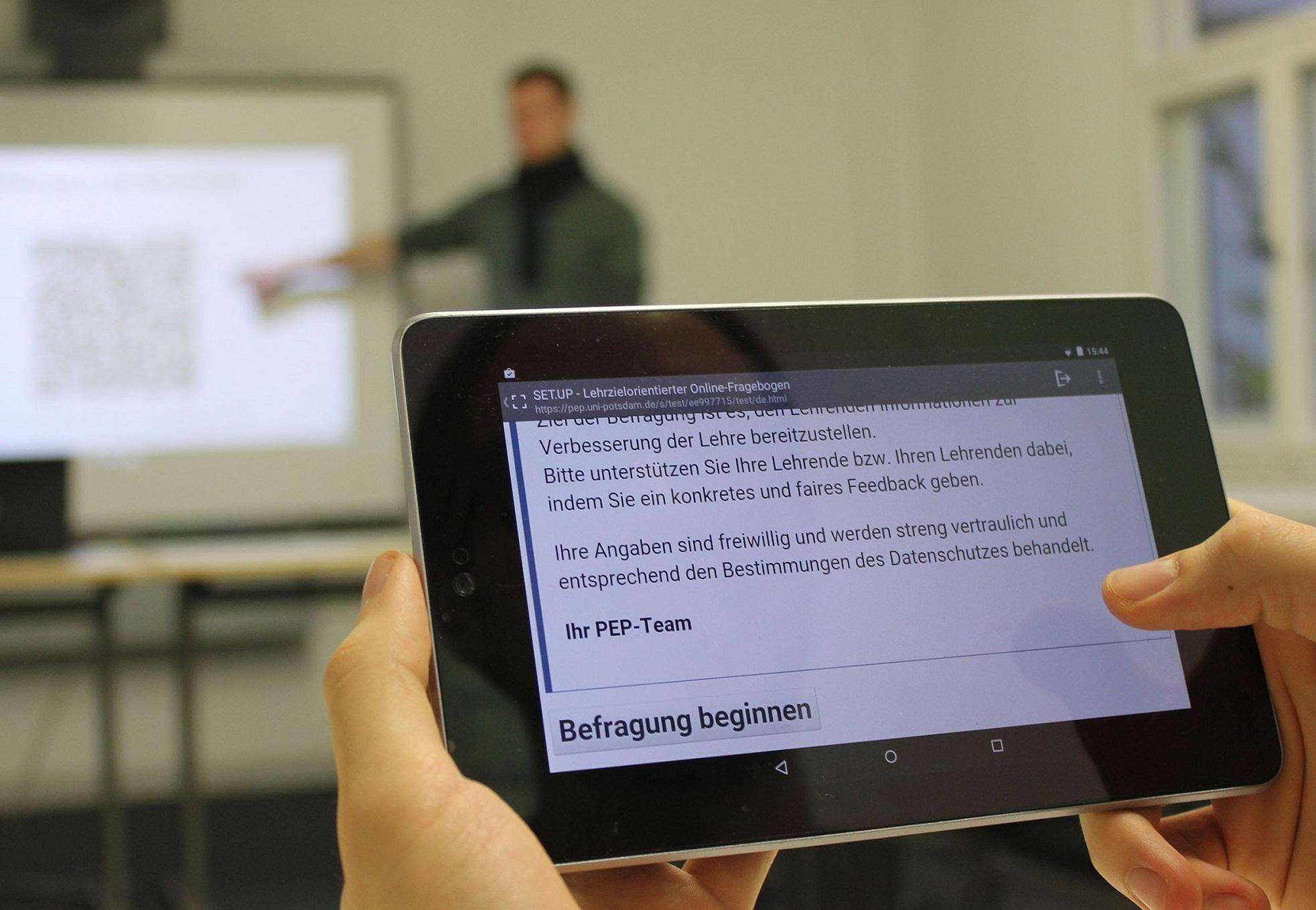 Tablet mit Startseite der Befragung, im Hintergrund steht ein Lehrender am Whiteboard und zeigt auf den QR-Code